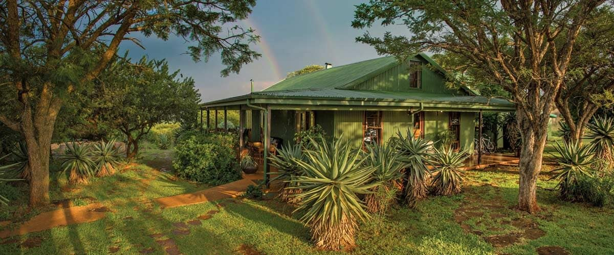 The front of the lodge with a rainbow behind it.