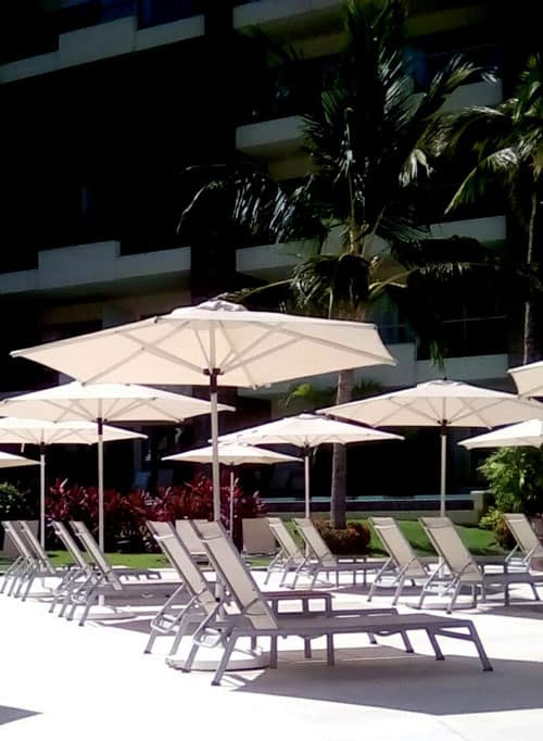 Groups of two pool loungers, a table and an umbrella, spaced 6-10 feet apart, were such an open space treat.