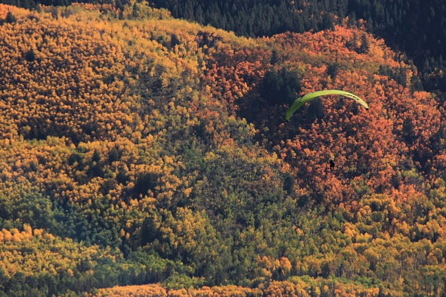 Paragliders combine a fall foliage fix with an adrenaline rush.  Photo by Clear Productions.