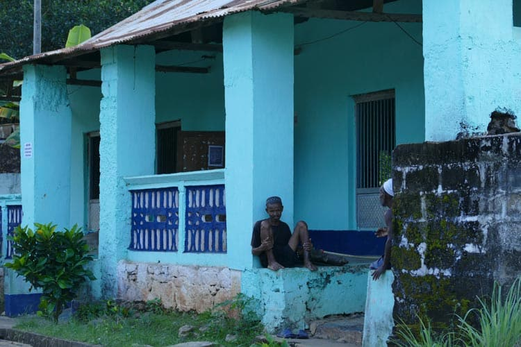 >A man sitting by the bright blue cottage in the village of Maradoka. Photo by Adrian Rorvik