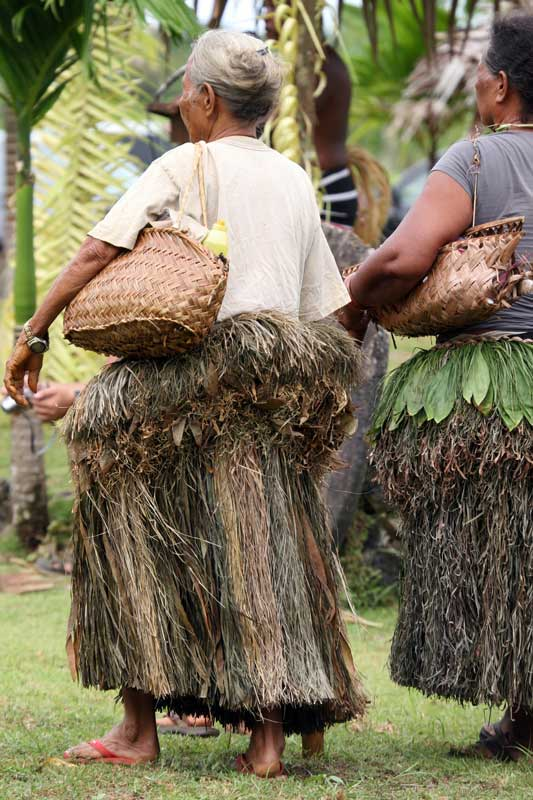 Yap women wearing traditional grass skirts and carrying handwoven baskets. Photo by Joyce McClure