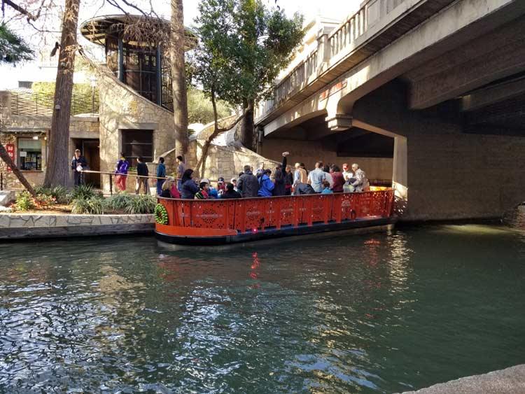 People enjoying a Go Rio Barge along the River Walk.