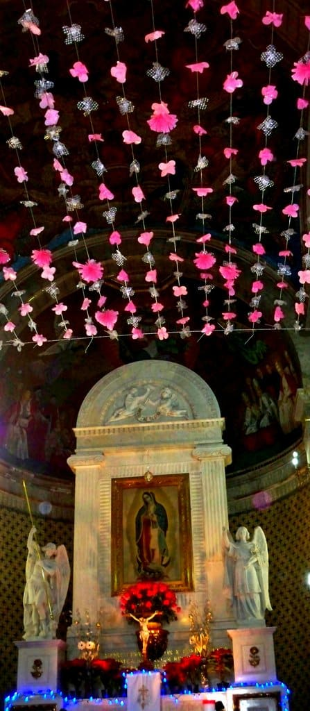 Flowers hang above a shrine dedicated to the Virgin of Guadalupe. Angels stand on both sides of the image while Jesus hangs below a vase of roses.