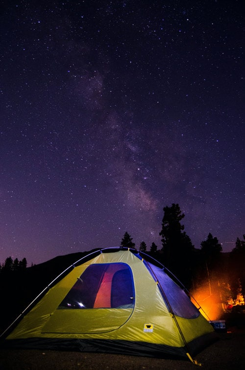 Tent illuminated underneath the night's star speckled sky