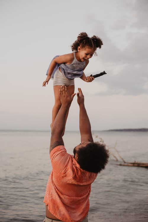 Dad throws daughter in the air on the beach