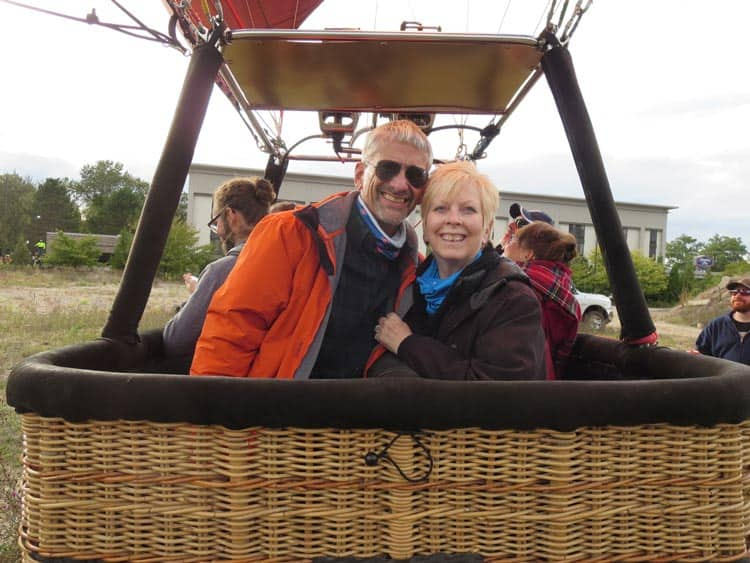A man and a woman pose smiling in a hot air balloon basket