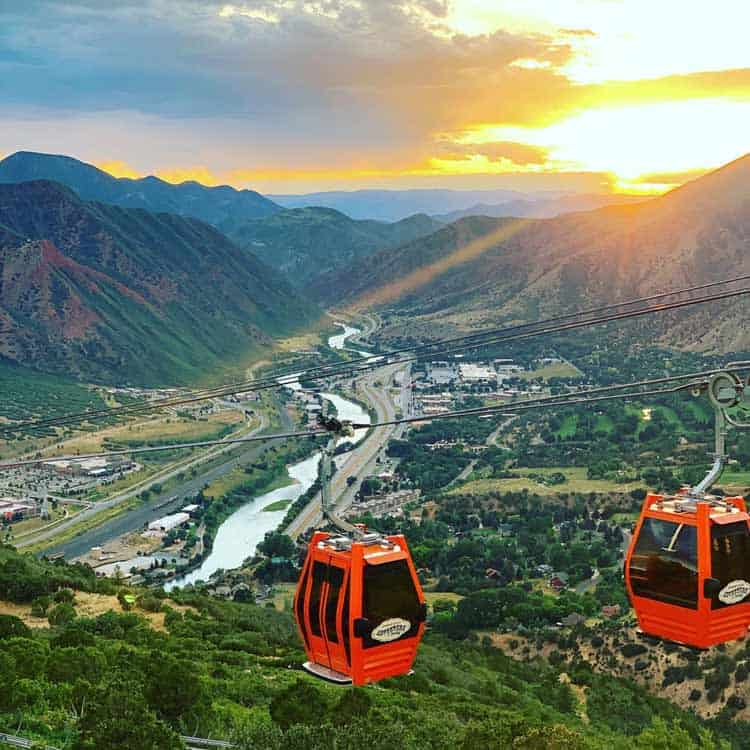Gondolas with a sunset and mountainside backdrop