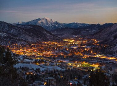 Picture of Glenwood Springs city lights nestled in between snowy mountain hills