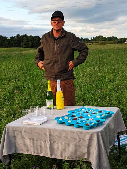 A man stands in a field in front of a clothed table with champagne, cups and cupcake trays