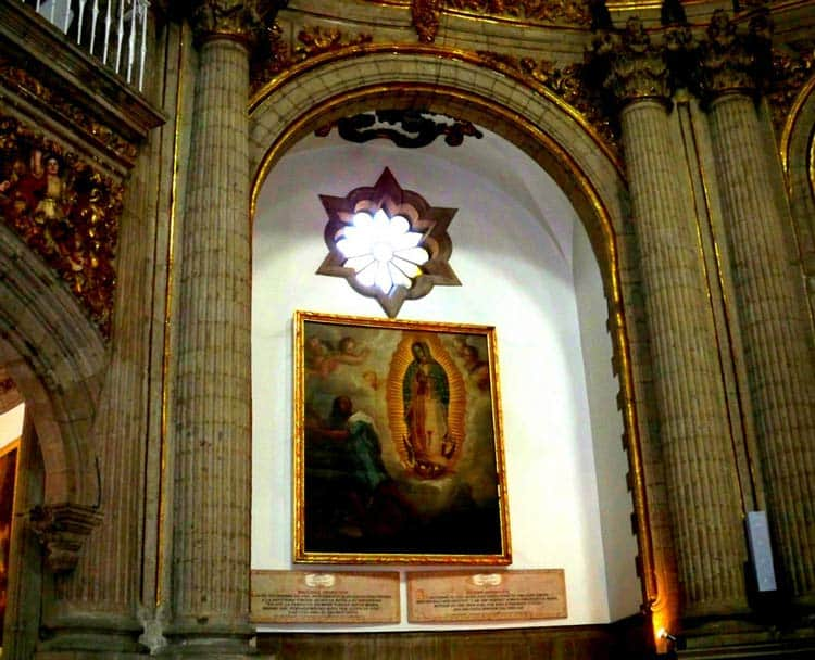 Image of the Virgin of Guadalupe hangs on a golden wall above the Mexican flag