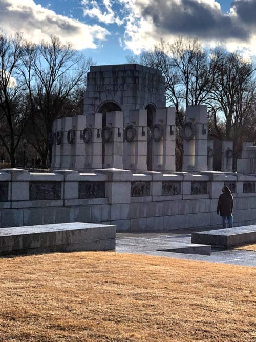 A person walks by the World War II Memorial under afternoon clouds