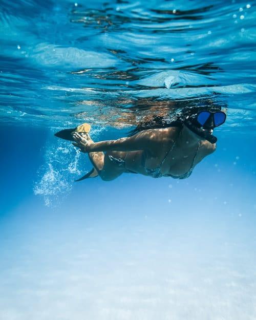 Woman snorkeling in clear blue water
