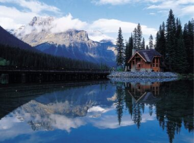 A log cabin near the lake in the mountains, reflecting the sky