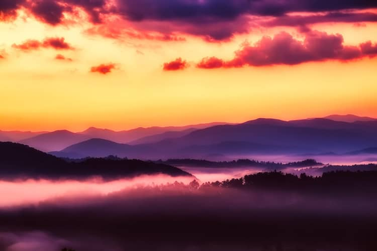 Shadowed and smoky mountain view with a fiery sky above