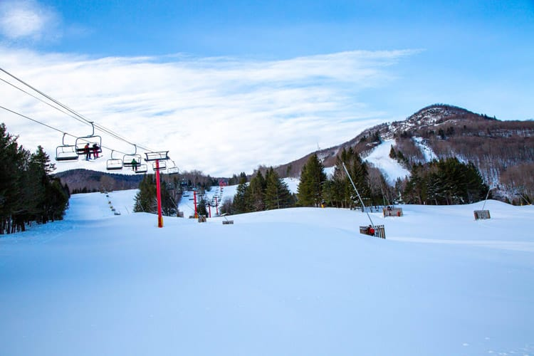 On the left, a ski lift with red poles among a snowy landscape in front of a mountain under a blue sky with wispy white clouds.