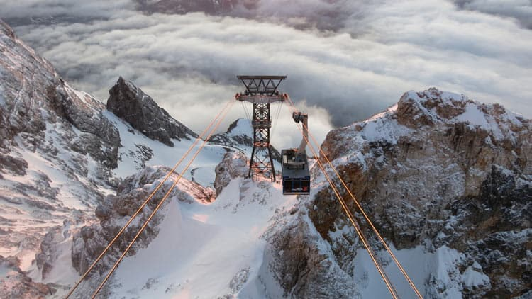 Travel by cable car up the snow-capped mountain in Germany