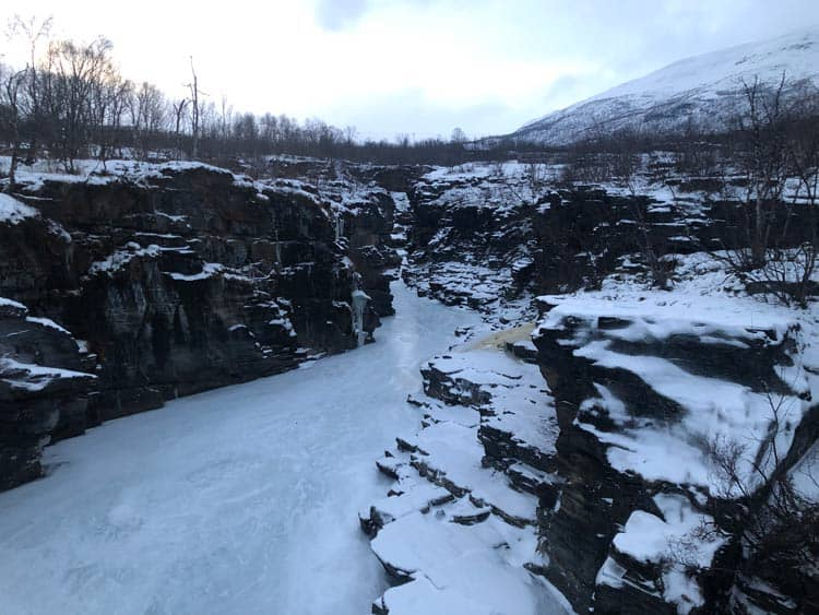 The sight of frozen waterfalls on your hike in Abisko, Sweden will leave you breathless. Photo by Esther Nampiina and Joseph Mukama