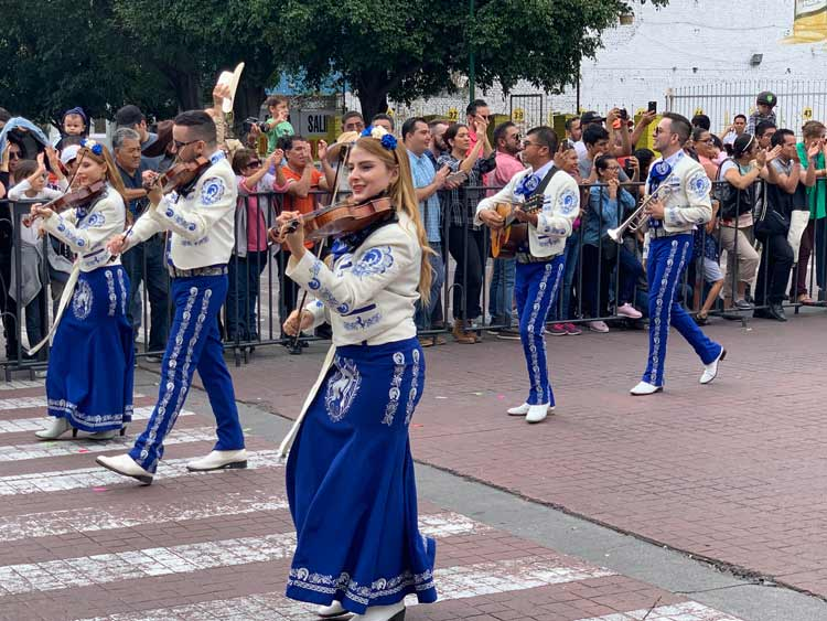 Mariachi bands parade down the street in a display of bright colors and traditional mariachi music. Photo by Maribeth Mellin