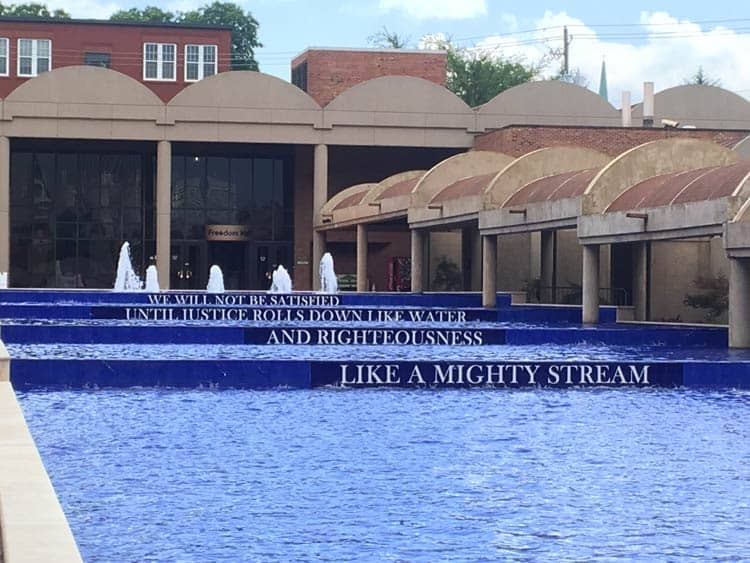 """Martin Luther King, Jr.'s famous words, """"We will not be satisfied until justice rolls down like water, and righteousness like a mighty stream"""" in the pool where his tomb is at The King Center in Atlanta, Georgia. Photo by Javier Ortega-Araiza"""