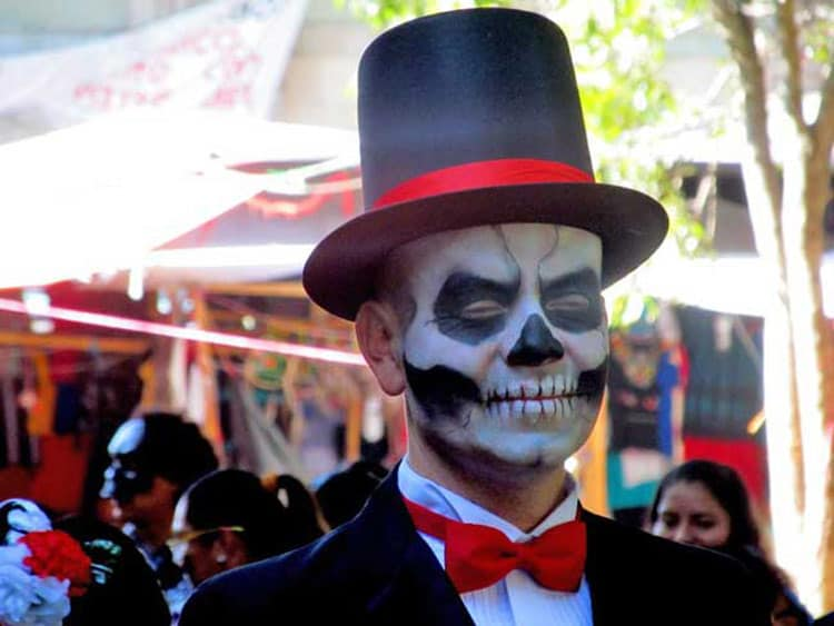 """A man playing the part of a """"Catrin"""" donned a top hat and tuxedo at Day of the Dead in Oaxaca, Mexico"""