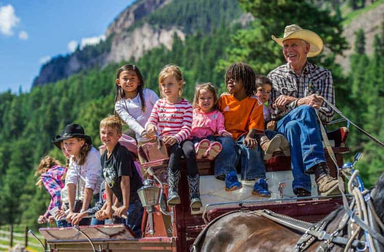 A wagon ride is a fun activity during a dude ranch family reunion