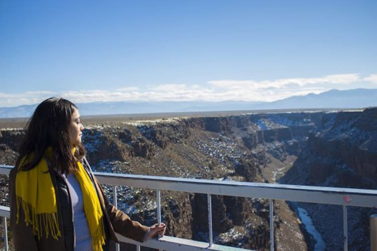 Gabriela Rodriguez holds onto the railing as she looks out over the Rio Grande Gorge. Photo by Sterling Stowe.