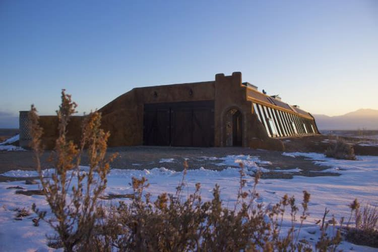 The front of the Earthship is made entirely of windows to let sunlight and heat into the house. Photo by Sterling Stowe.