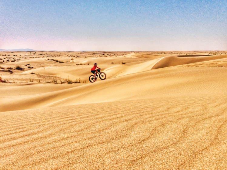 Kate Leeming cycling sand dunes on Namibia's Skeleton Coast