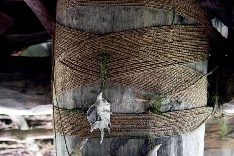 Interior of family home with rope lashings holding shell money. Photo by Joyce McClure