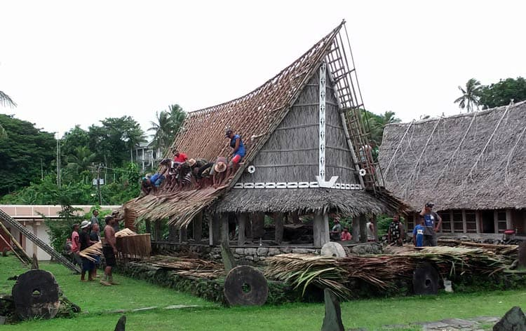 Putting a new thatch roof on men's house. Photo by Joyce McClure
