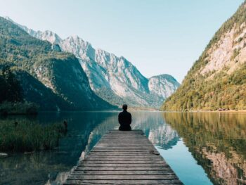 Contemplative person sitting at edge of mountain lake. Photo by Simon Migaj