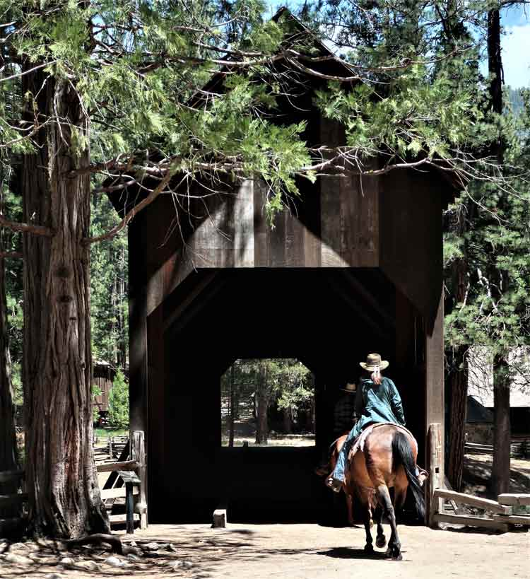 A horseback rider enters the covered bridge at the Pioneer Yosemite History Center. Photo by Victor Block