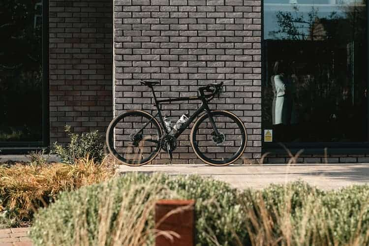 Bicycle against brick wall by Tom Austin