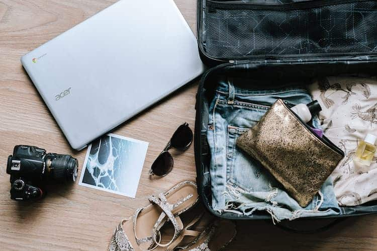 Open suitcase with miscellaneous travel items by Anete Lusina