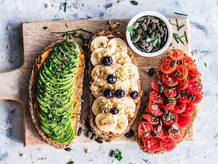 3 pieces of toast topped with avocado banana and tomato by Ella Olsson